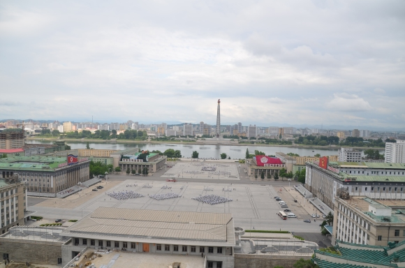 Juche Tower in the distance. In the middle ground are people practicing for the games this fall.