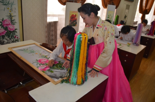 A teacher instructs a student in embroidery