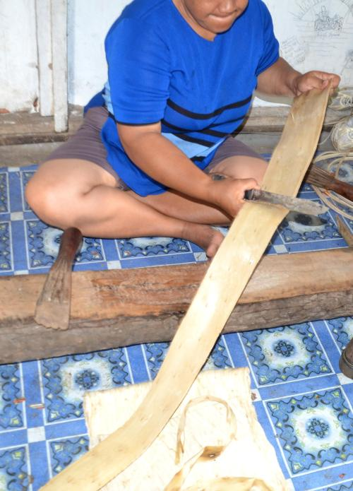 Hammering flat another piece of paper mulberry wood and removing the bark.