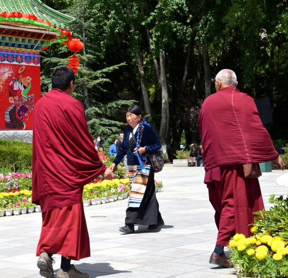 Tibetan lady in her native attire passes 2 Tibetan monks in the park.
