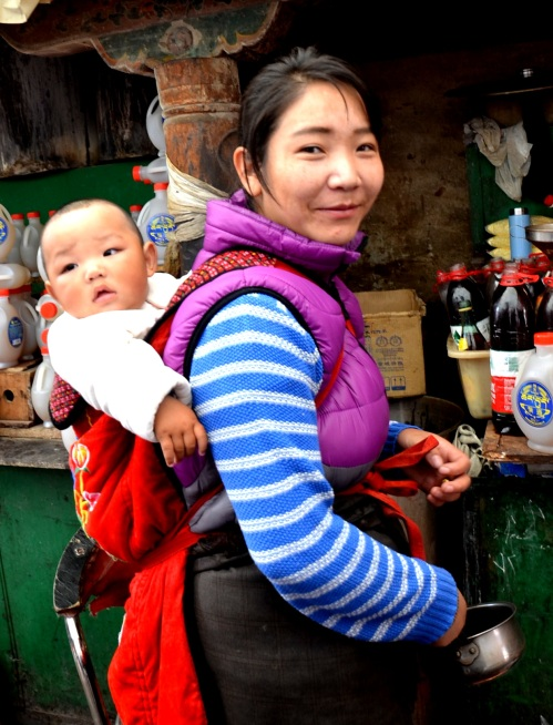 This young lady, with her precious little baby on her back, sold items at the Jokhang Temple.